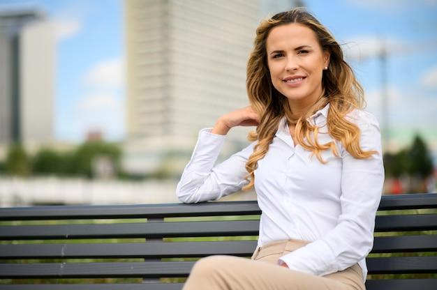 Donna bionda che si distende su una panchina del parco Foto Premium