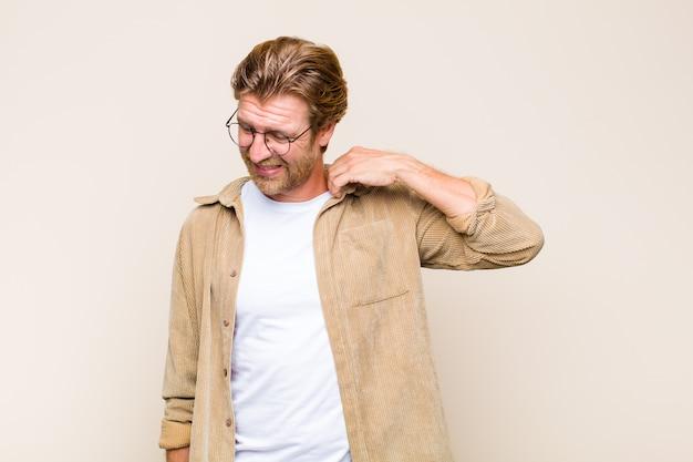 Uomo adulto biondo che si sente stressato, ansioso, stanco e frustrato, tira il collo della camicia, sembra frustrato dal problema Foto Premium