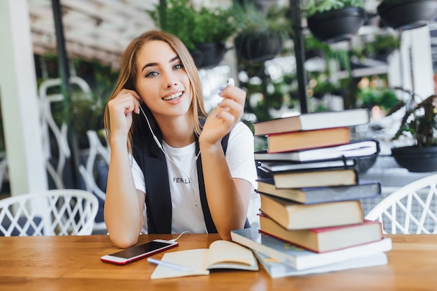 Bionda imprenditrice con libri in ufficio Foto Premium