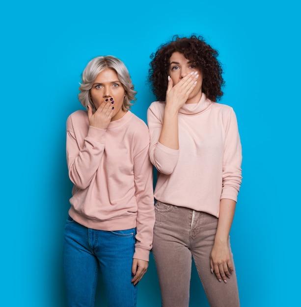 Signora caucasica bionda che gesturing il segno di stupore vicino alla sua amica bruna dai capelli ricci mentre posa su una parete blu con uno spazio vuoto Foto Premium