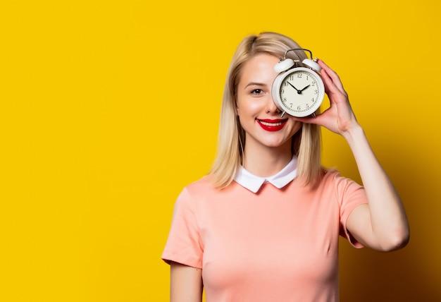 Ragazza bionda in vestito rosa con la sveglia su spazio giallo Foto Premium