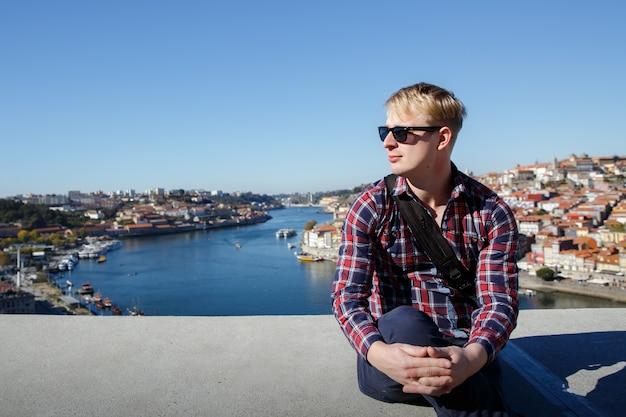 Una bionda è seduta su una città europea. occhiali da sole, camicia a quadri Foto Premium