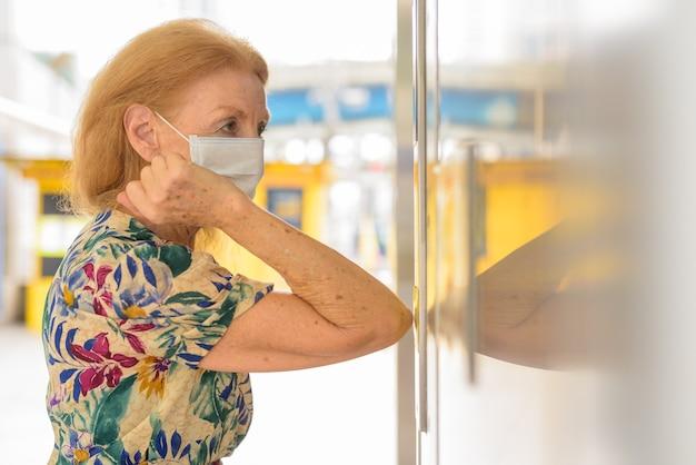 Donna anziana bionda con maschera che preme il pulsante dell'ascensore con il gomito per evitare di diffondere il coronavirus covid-19 Foto Premium
