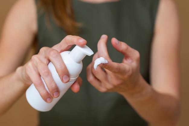 Donna bionda che applica una crema a disposizione Foto Premium
