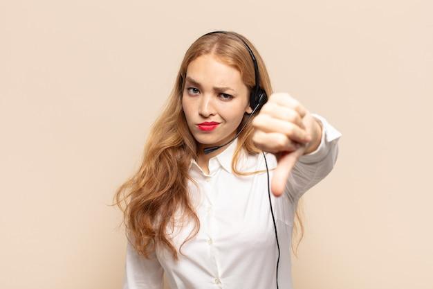 Donna bionda che si sente arrabbiata, arrabbiata, infastidita, delusa o scontenta, mostrando i pollici verso il basso con uno sguardo serio Foto Premium