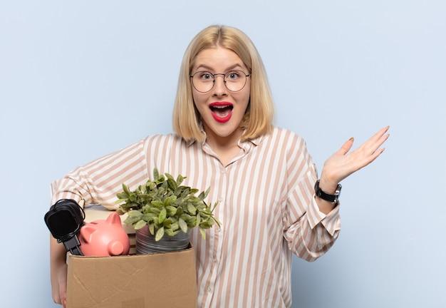 Donna bionda che si sente felice, eccitata, sorpresa o scioccata, sorridente e stupita da qualcosa di incredibile Foto Premium