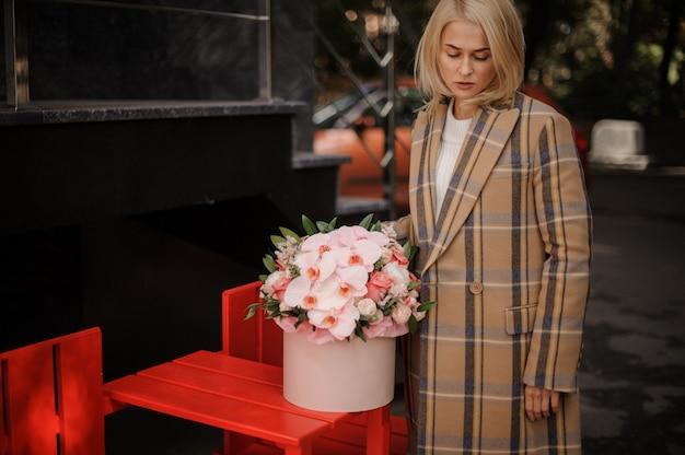Donna bionda in cappotto autunno plaid con una scatola di fiori rosa Foto Premium
