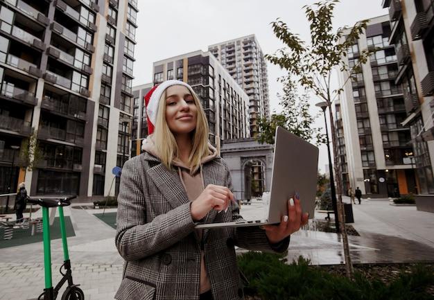 Donna bionda in cappello di babbo natale che indossa abiti casual seduti fuori e lavorando sul suo computer portatile. buon natale e felice anno nuovo! giovane donna freelance facendo il suo lavoro sull'aria fresca. Foto Premium