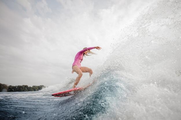 Surfista biondo della donna che guida giù l'onda di spruzzatura blu contro il cielo grigio Foto Premium