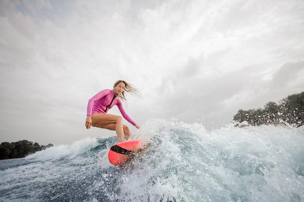 Surfista biondo della donna che guida giù l'onda di spruzzatura blu contro il cielo Foto Premium