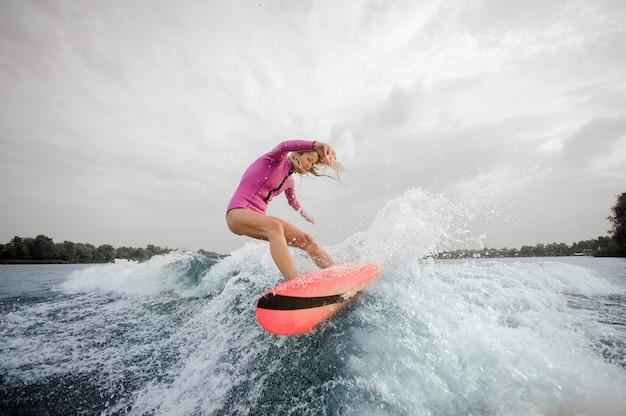 Surfista biondo della donna che guida giù l'onda di spruzzatura blu Foto Premium