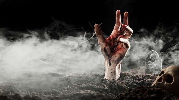 Mano di sangue che spunta da terra nella nebbia Foto Premium