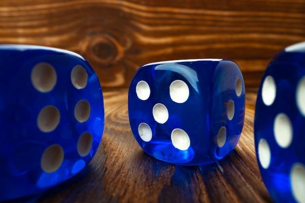 Cubi di dadi blu su sfondo di legno marrone da vicino foto Foto Premium