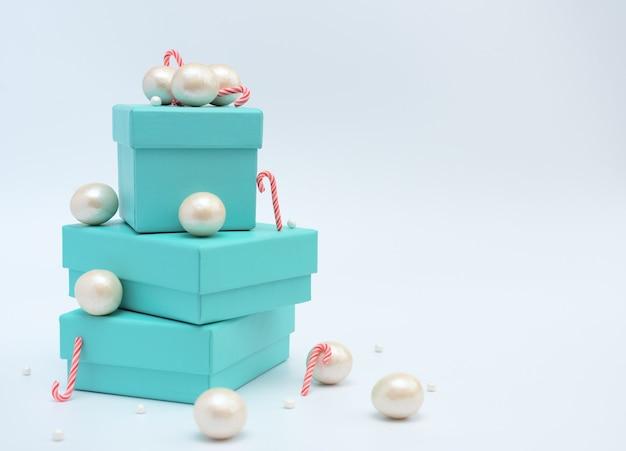 Scatole regalo blu con bastoncini di natale, perle grandi e piccole su bianco Foto Premium