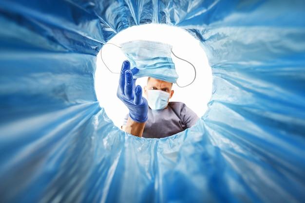 Un uomo con i guanti blu getta una maschera medica usata nella spazzatura, una vista dal secchio. concetto di smaltimento dei rifiuti sanitari e conseguenze della protezione dalla diffusione del virus Foto Premium
