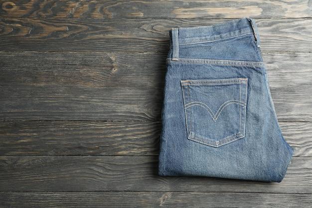 Le blue jeans hanno piegato su un fondo di legno, spazio per testo Foto Premium