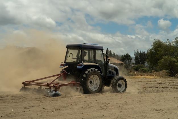 Un trattore blu che ara un campo in una giornata polverosa Foto Premium
