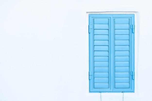 Persiane blu su un muro bianco. spazio per il testo Foto Premium