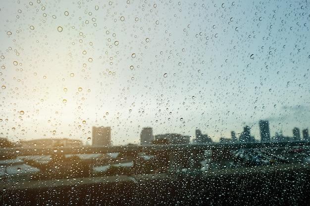 Goccia sfocata in finestrini dell'auto e luce del sole sulla città del mattino Foto Premium