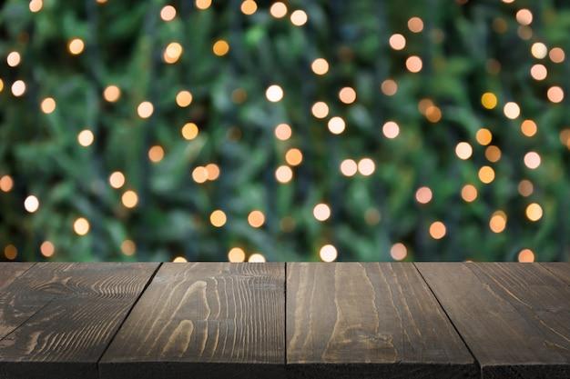 Ghirlanda d'oro sfocata sull'albero di natale come sfondo e piano in legno come primo piano. estratto di natale. immagine per visualizzare o montare i tuoi prodotti natalizi. copia spazio. Foto Premium
