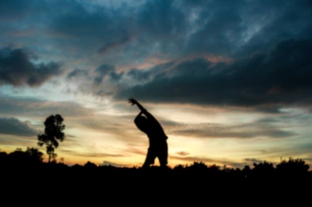 Movimento sfocato fitness on sunrise silhouette un uomo di allenamento uomo Foto Premium