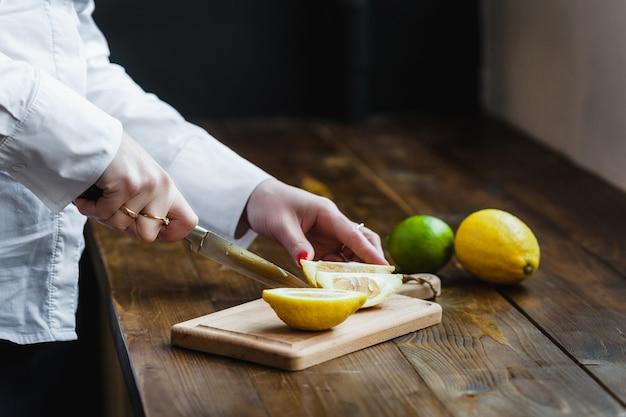 Tavola con limone e lime per affettare, preparare per cucinare, insalate e antipasti, succo di limone, decorare piatti, cucinare, uomo che taglia un limone, con in mano un coltello da cucina, tagliare un lime Foto Premium