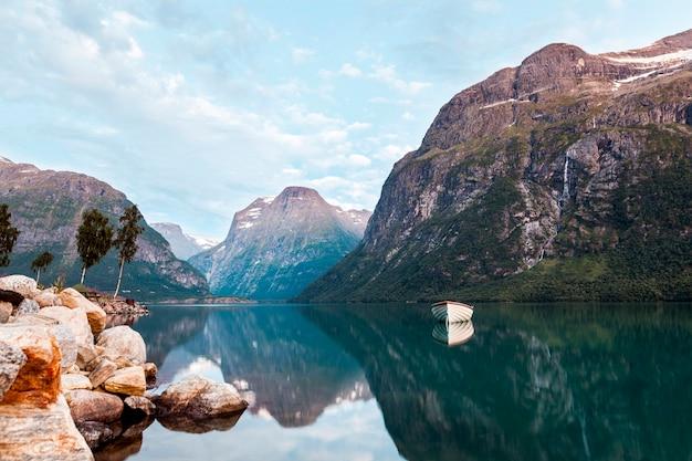 Barca ormeggiata nel lago calmo di un paesaggio da sogno con la bella montagna Foto Premium