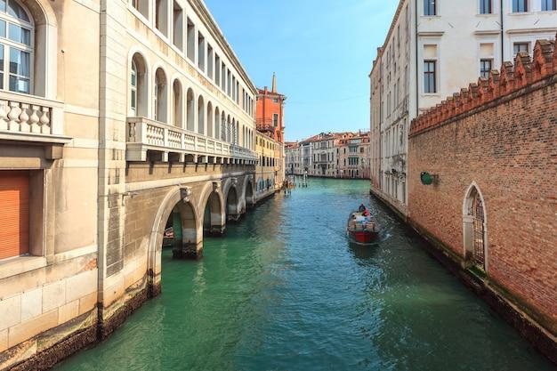 Barche sul canale stretto tra case storiche colorate a venezia. Foto Premium