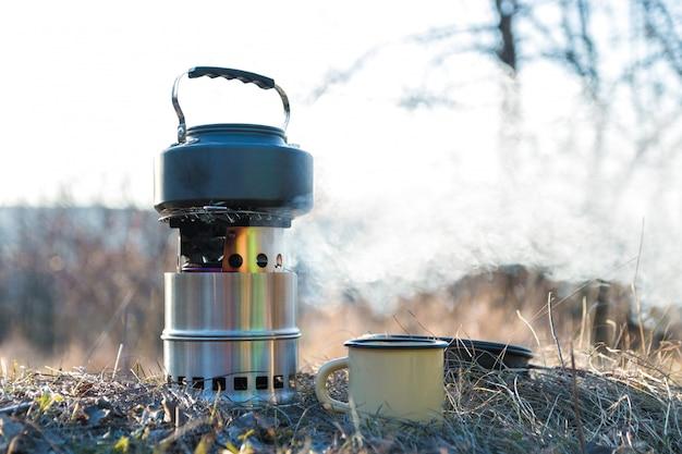Acqua bollente in bollitore sul bruciatore a legna portatile con fumo. preparazione del tè all'aperto Foto Premium