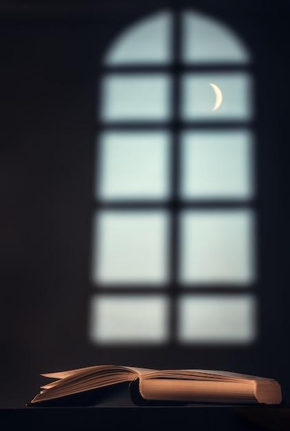 Libro (bibbia, corano) sul tavolo contro la finestra di una grande finestra e una mezzaluna Foto Premium