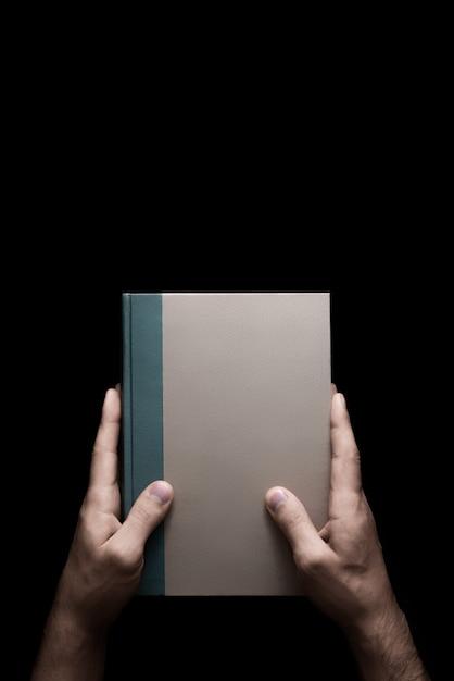 Prenota in mani maschili su uno sfondo nero 1 di 7 Foto Premium