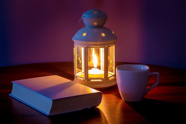 Un libro con una copertina bianca vicino alla lanterna e una tazza di caffè la sera Foto Premium