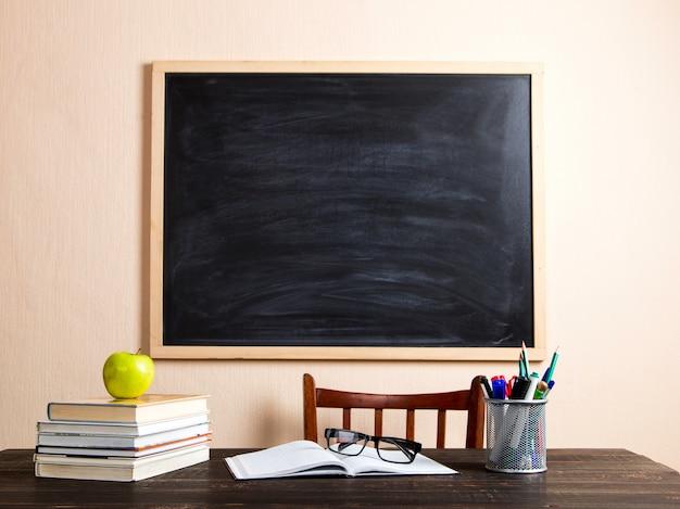 Libri, mela, penne, matite e bicchieri su un tavolo di legno, contro un bordo di gesso. Foto Premium