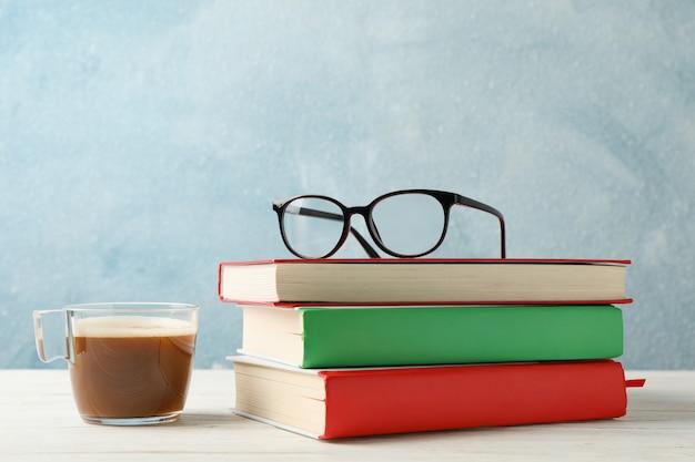 Libri, bicchieri e tazza di caffè contro lo spazio blu, spazio per il testo Foto Premium
