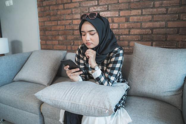Donna annoiata a casa usando il suo telefono cellulare Foto Premium