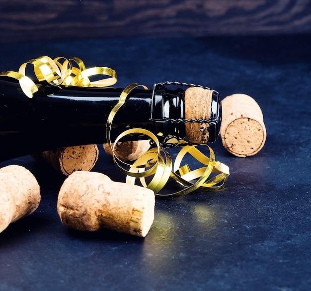 Bottiglia di champagne e una serie di tubi, concetto di vacanza, sfondo scuro Foto Premium