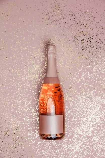 Bottiglia di champagne con glitter oro rosa sfondo, vista dall'alto Foto Premium