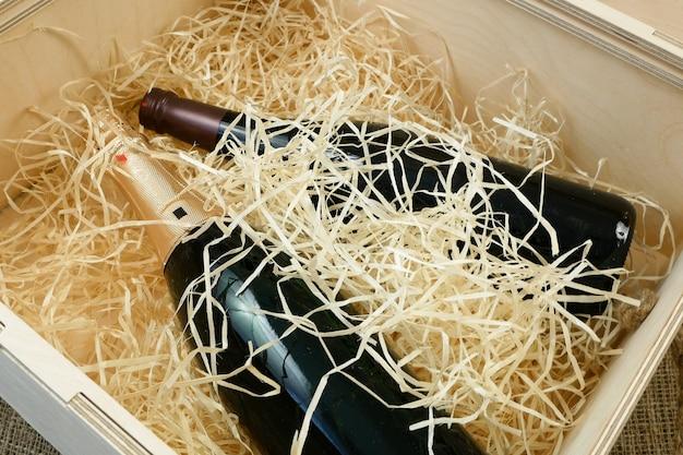 Bottiglia di vino d'élite costoso in una scatola di legno Foto Premium
