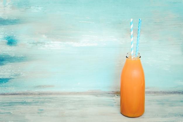 Una bottiglia di succo fresco con due cannucce davanti a uno sfondo blu rustico. copia spazio, mock-up. Foto Premium