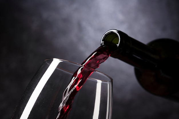 Bottiglia che versa vino rosso in vetro Foto Premium