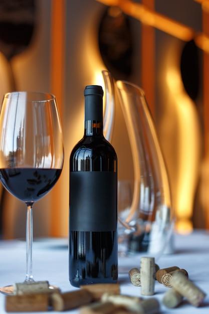 Bottiglia di vino rosso, un bicchiere di vino e un decanter su un tavolo con una tovaglia bianca. Foto Premium
