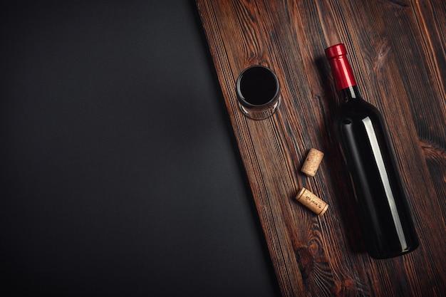 Bottiglia di tappi per vino e bicchiere di vino su sfondo arrugginito Foto Premium