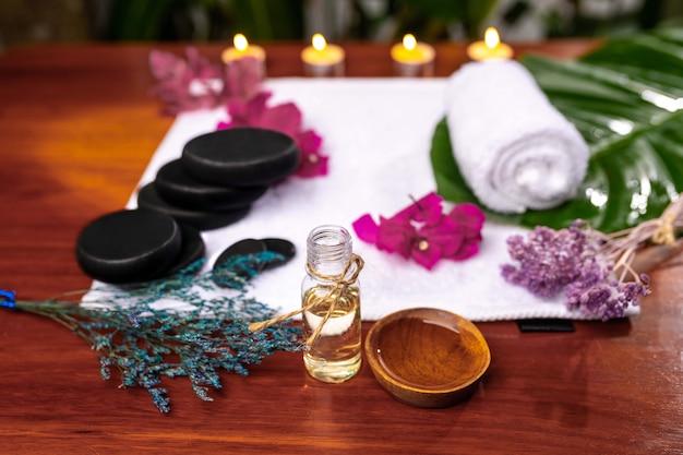 Una bottiglia con olio aromatico, una tazza con olio versato situata di fronte a un asciugamano di spugna su cui sono pietre per pietra terapeutica, un asciugamano arricciato, fiori rosa e rametti di lavanda essiccati Foto Premium