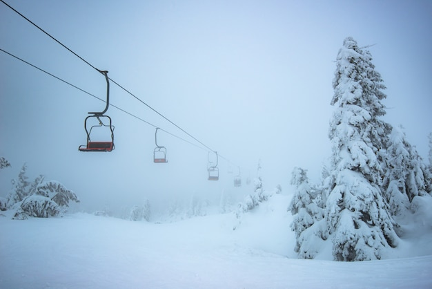 Vista dal basso ascensori turistici vuoti pendono sopra le colline Foto Premium