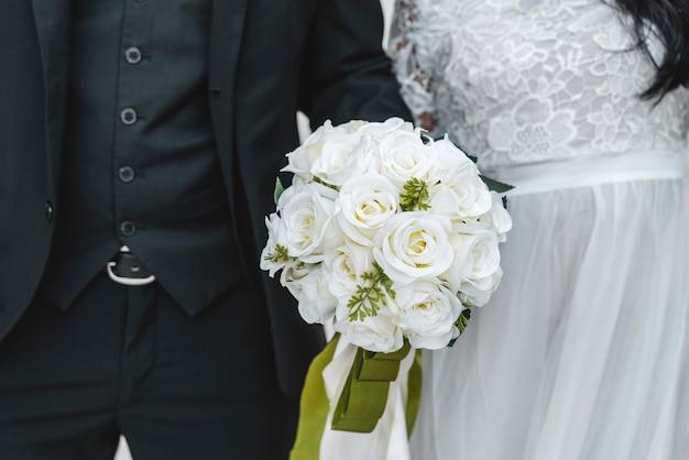 Bouquet di fiori tenuto da sposo e sposa Foto Premium