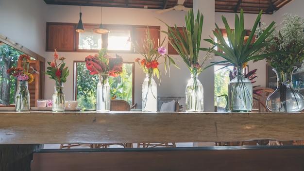 Mazzo di fiori e foglie nel vaso sul tavolo di legno Foto Premium