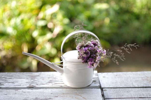 Mazzo di fiori in un annaffiatoio sulla tavola di legno Foto Premium