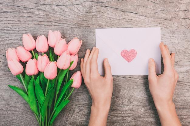 Il mazzo dei tulipani rosa e le mani delle donne tengono una busta in bianco con un cuore, su un fondo di legno. Foto Premium