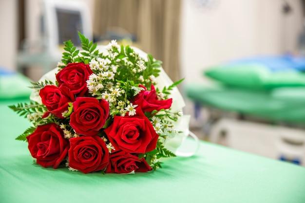 Un mazzo di rose su un letto d'ospedale Foto Premium