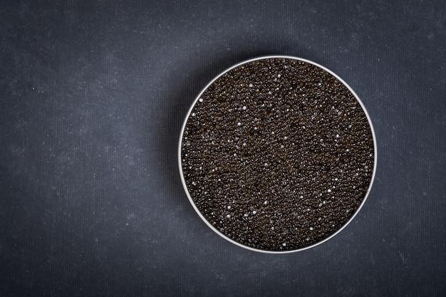 Ciotola di caviale nero di storione su una superficie blu scuro.vista dall'alto Foto Premium
